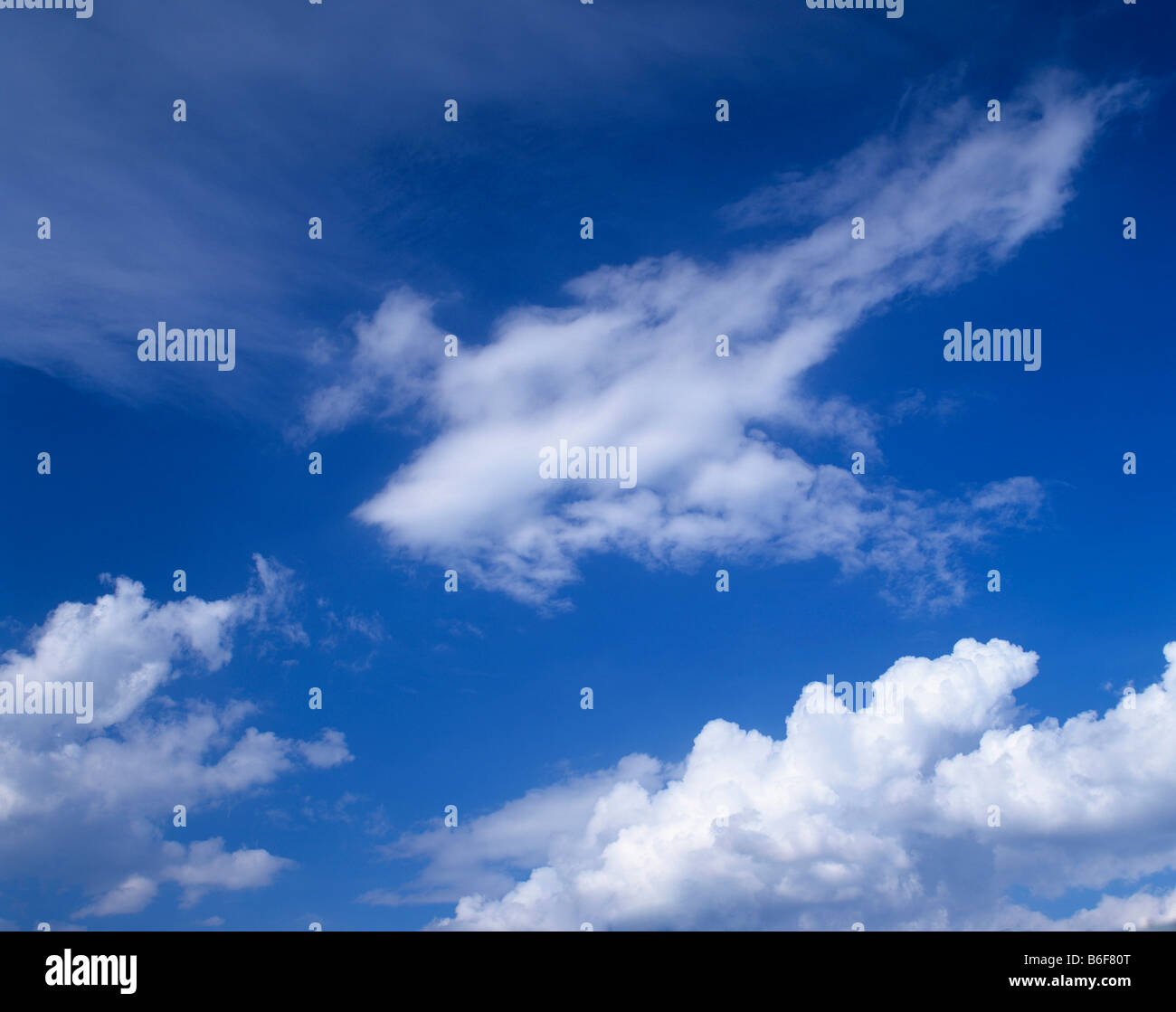 Cumulus and cirrostratus clouds in a blue sky - Stock Image