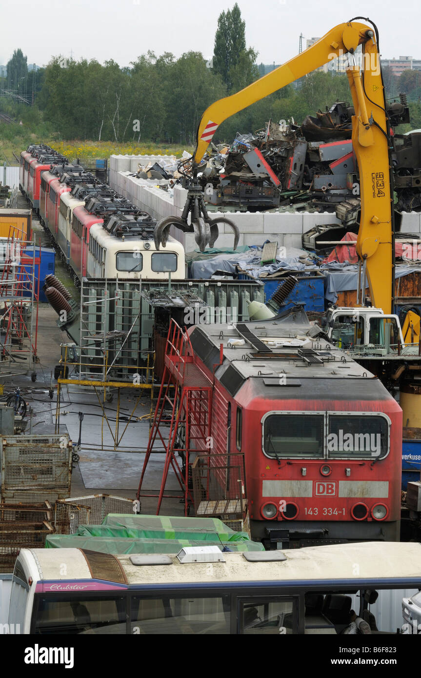 View of scrap yard, recycling yard, 9 E-locomotives, large gripper for junk, utilization of metal - Stock Image