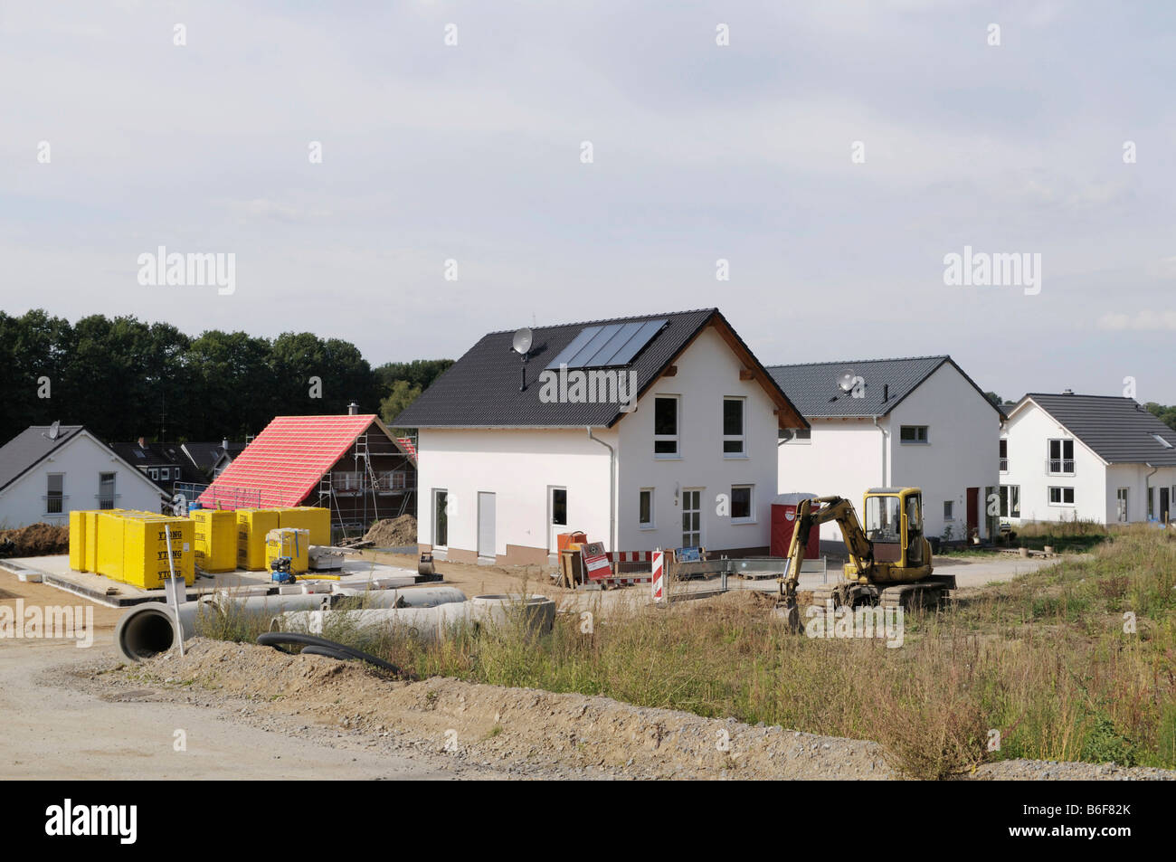 View of new housing estate, in front sewer pipes and an excavator for development, Solingen, North Rhine-Westphalia, - Stock Image