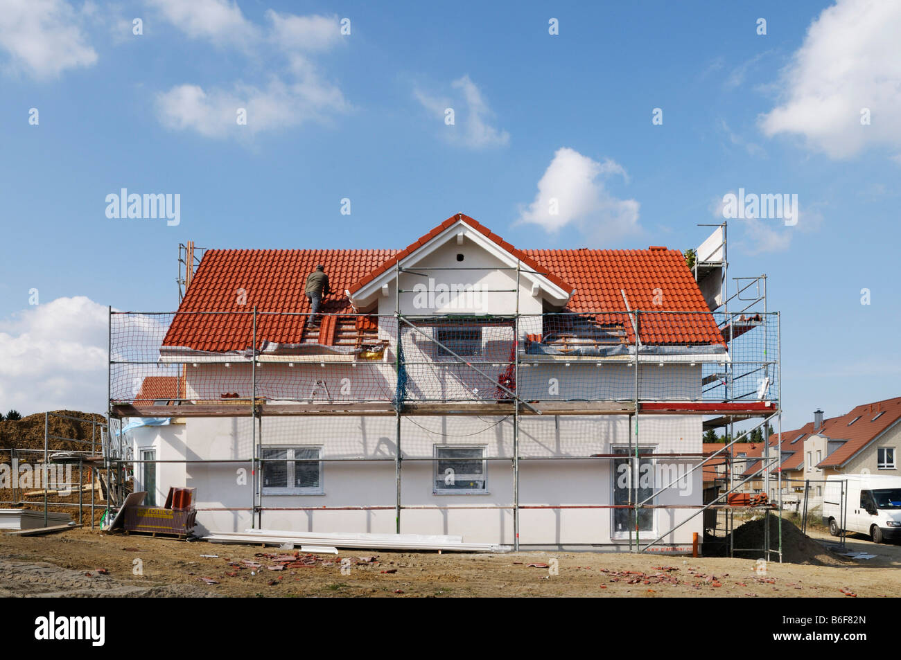 Newly constructed house with scaffolding, roofer laying roof tiles, Mettmann, North Rhine-Westphalia, Germany, Europe - Stock Image