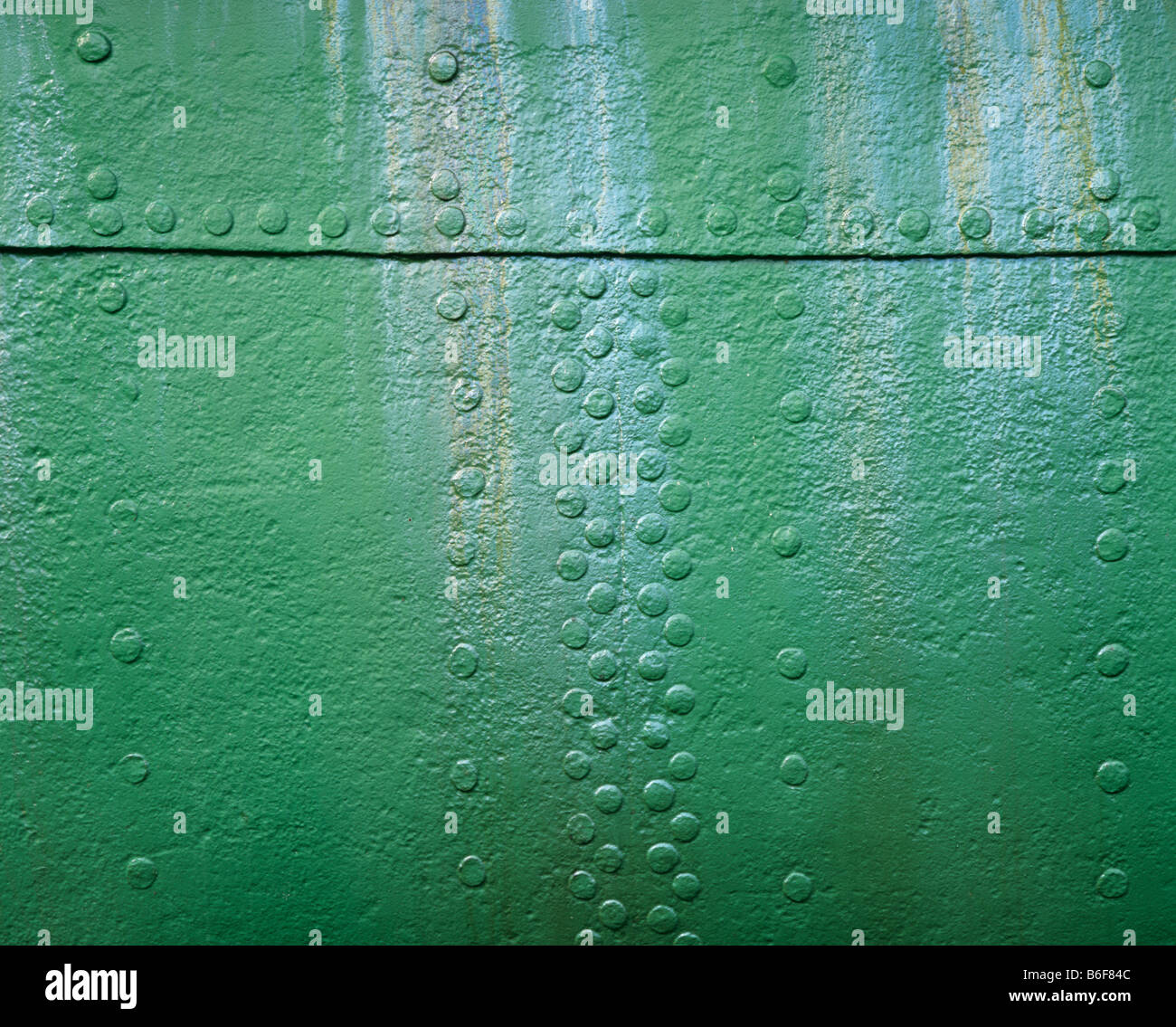 Riveted green metal surface with oil streaks - Stock Image