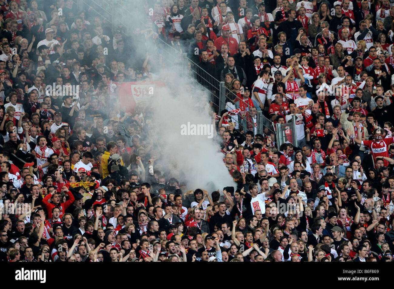 Hooligans igniting fireworks and smoke bombs in a fan block - Stock Image