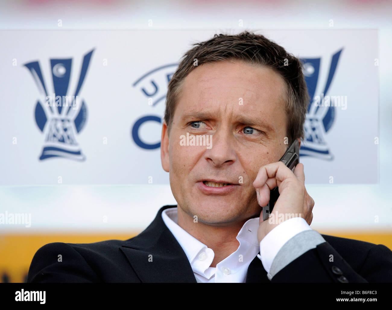 Manager Horst HELDT, VfB Stuttgart on his mobile, UEFA-Cup logo behind him, Stuttgart, Germany, Europe Stock Photo
