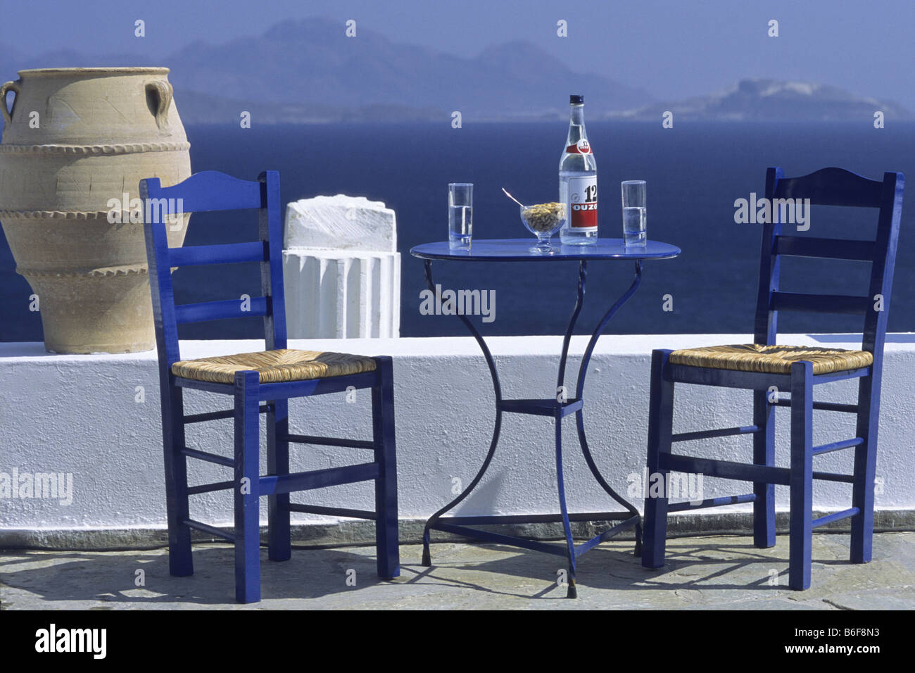 Merveilleux Blue Chairs And Table With Ouzo Bottle In Front Of White Wall, Mediterranean  In Background, Greece, Kos