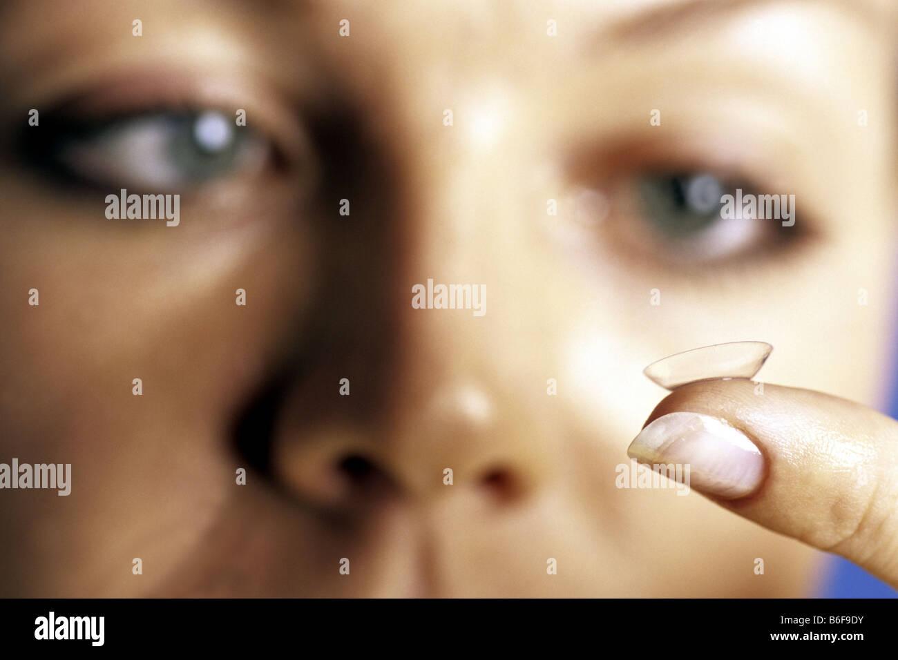 woman looking at contact lense - Stock Image
