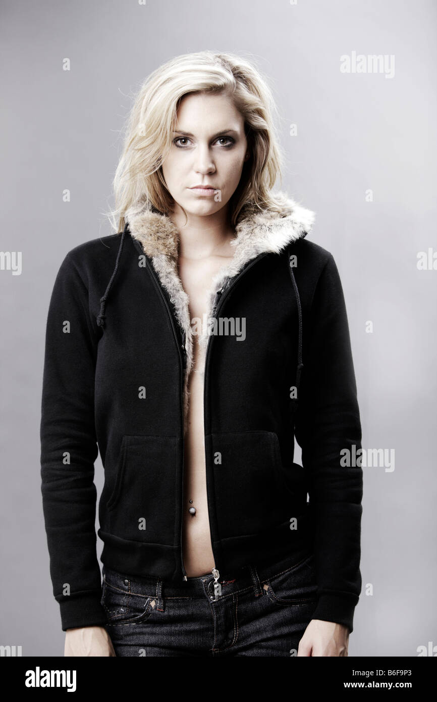 Blond woman wearing a fur-lined hooded jacket - Stock Image