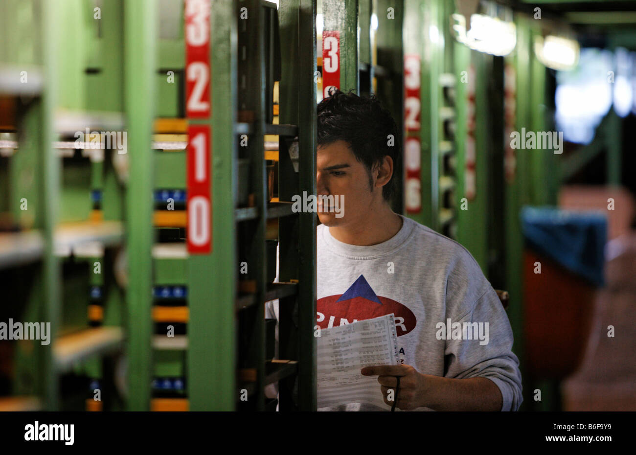 Skilled worker for stock management and logistics in the spare parts store of Daimler AG, Mercedes Benz Plant in - Stock Image