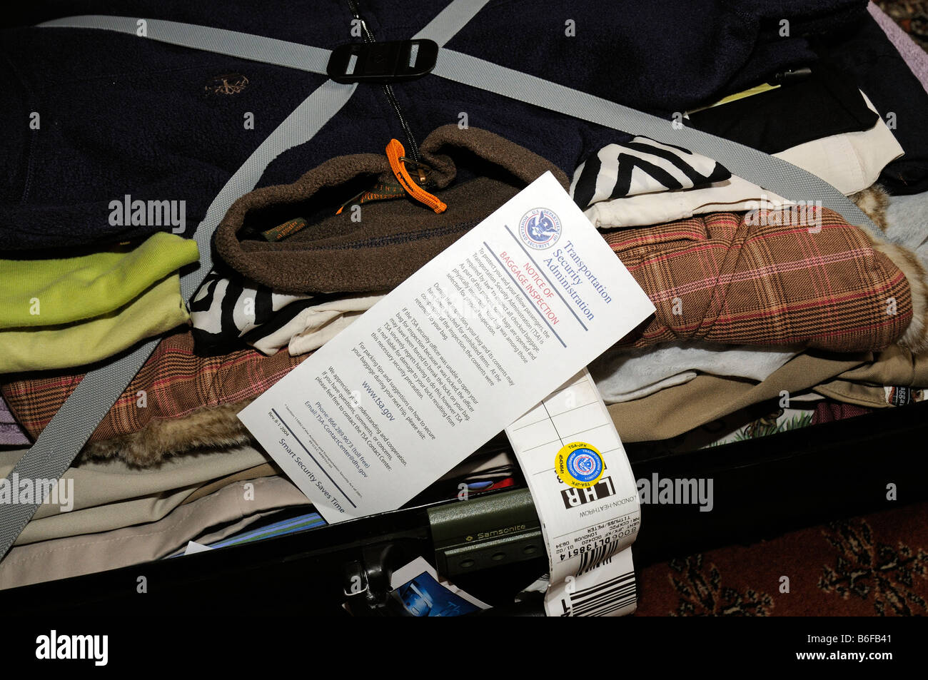 US Department Homeland Security notice of baggage inspection inside an open suitcase - Stock Image