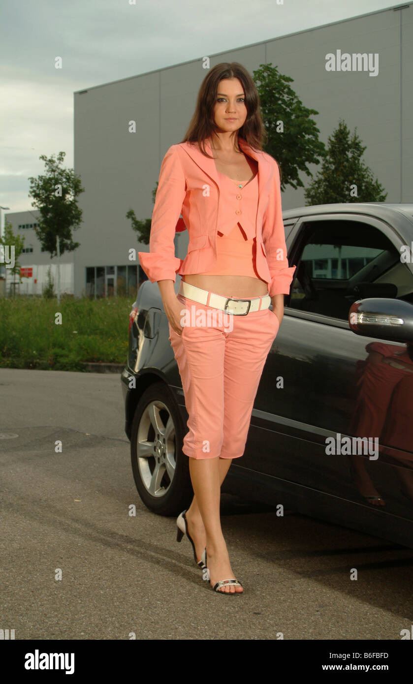 Young woman in a pink suit stands in front of her car Stock Photo