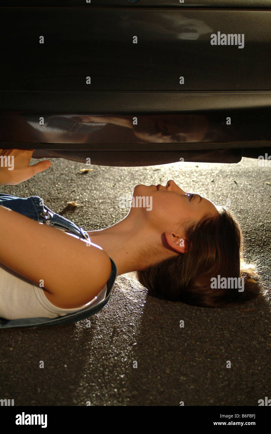 Young woman in working clothes is lying under her car while fixing it - Stock Image