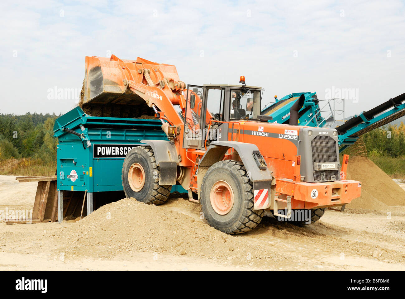 Wheeled loader putting gravel into a mobile sieving plant - Stock Image