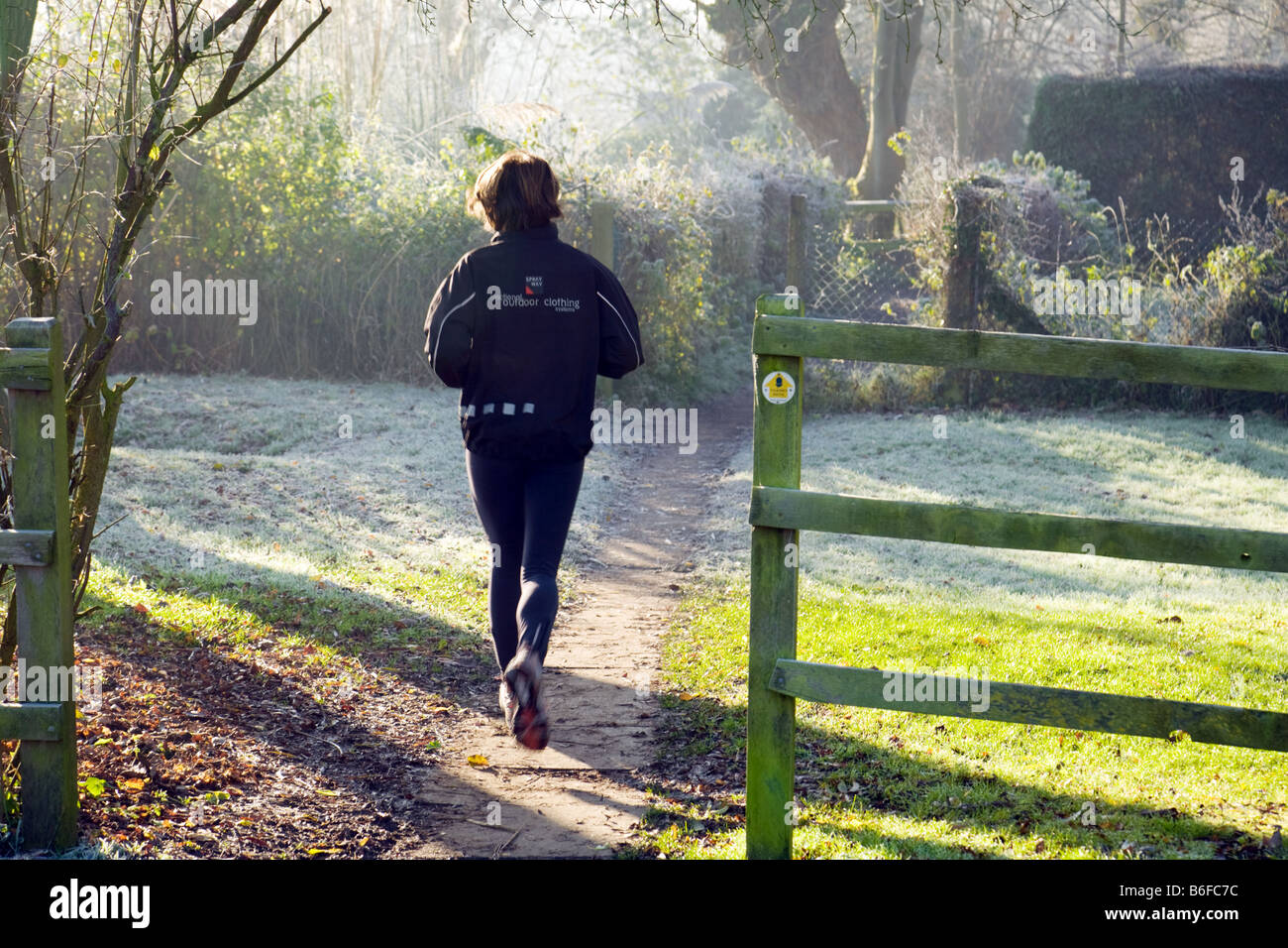 A woman jogger jogging on the Thames Path on a winter morning, Wallingford, Oxfordshire UK - Stock Image