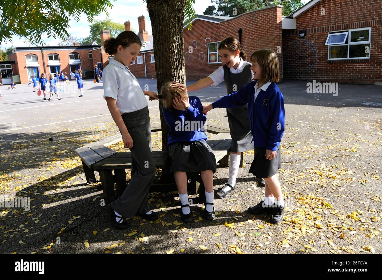 School playground schoolgirl being bullied by classmates - Stock Image