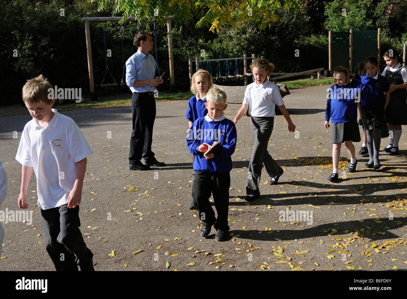 Schoolchildren walking in line in a school playground - Stock Image