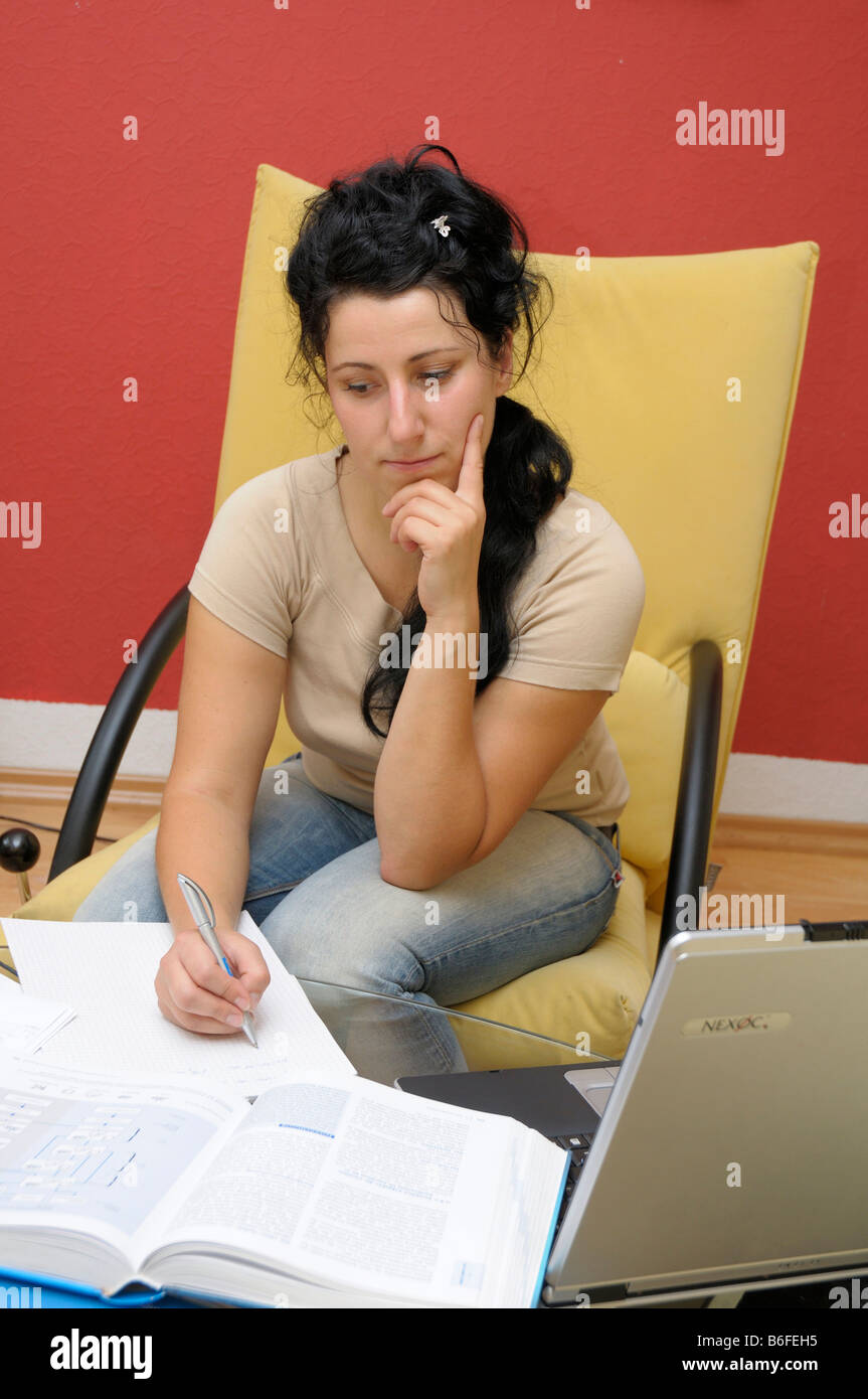 Young woman, 28, studying - Stock Image