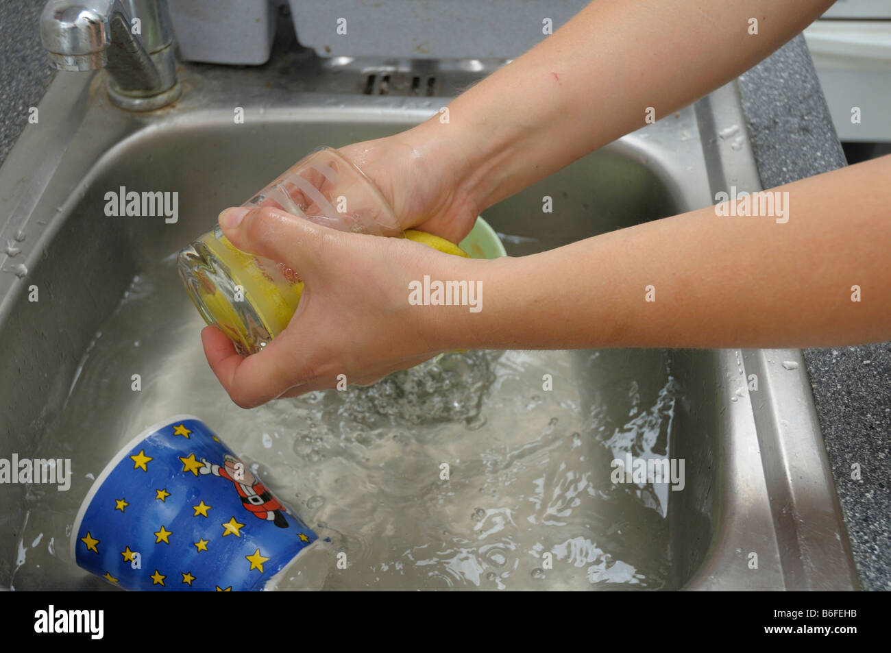 Housework, young woman, 28, doing the washing-up - Stock Image
