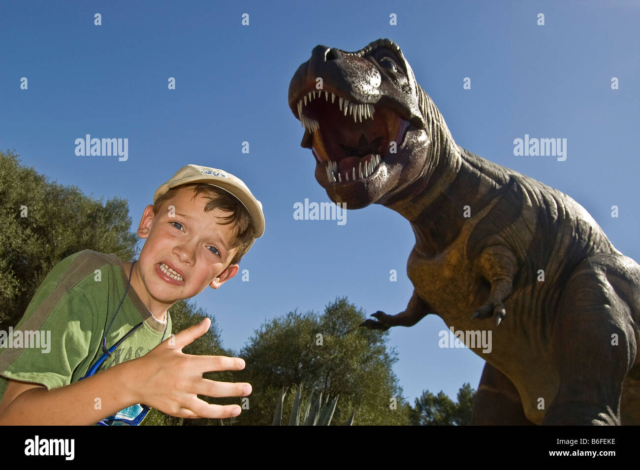 Boy with a dummy of a Dinosaur (Tyrannosaurus Rex), Majorca, Balearic Islands, Spain, Europe - Stock Image