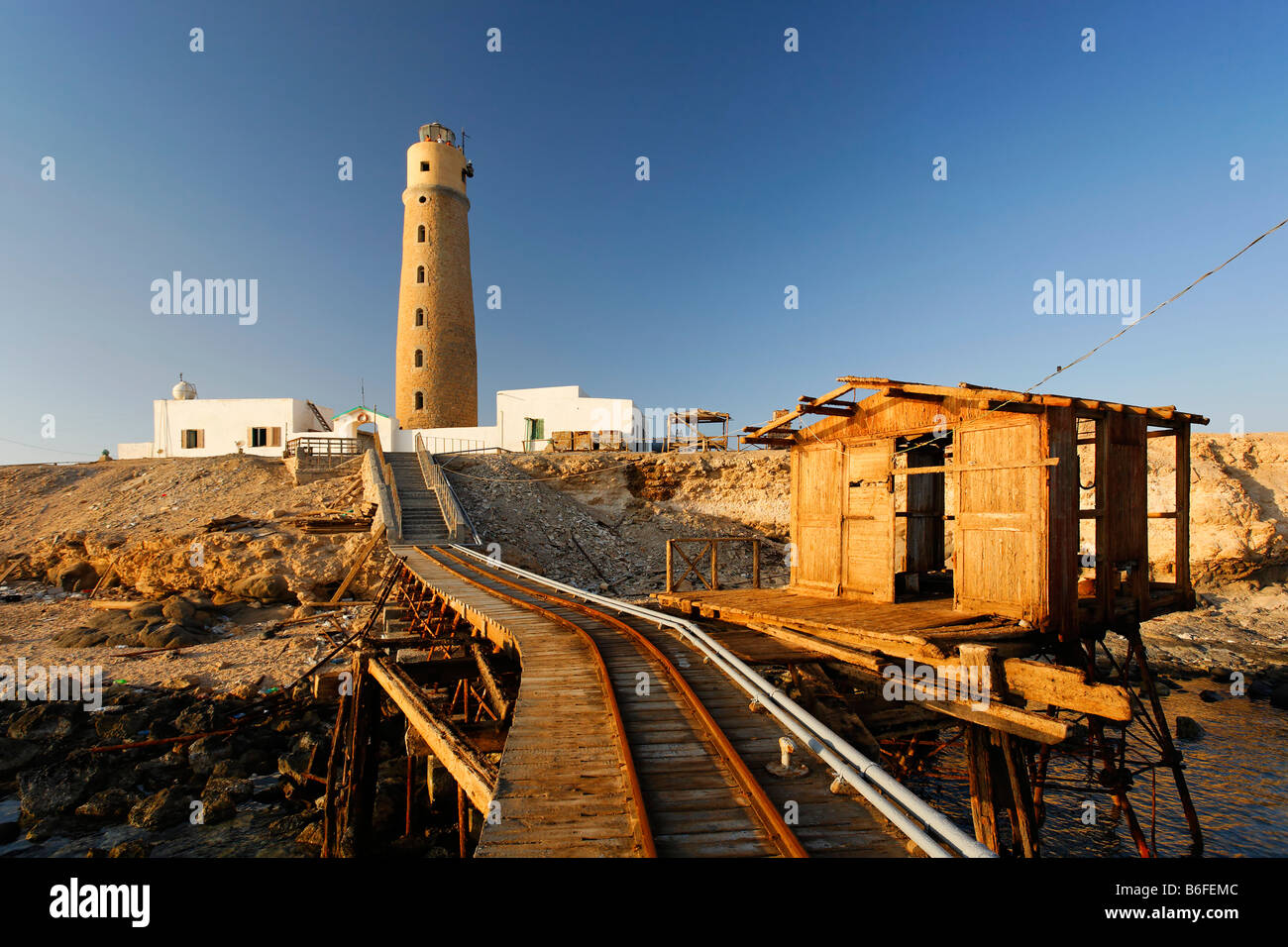 Railway tracks on a pier leading past a hut to a lighthouse on the Big Brother of The Brothers Islands or El Akhawein - Stock Image