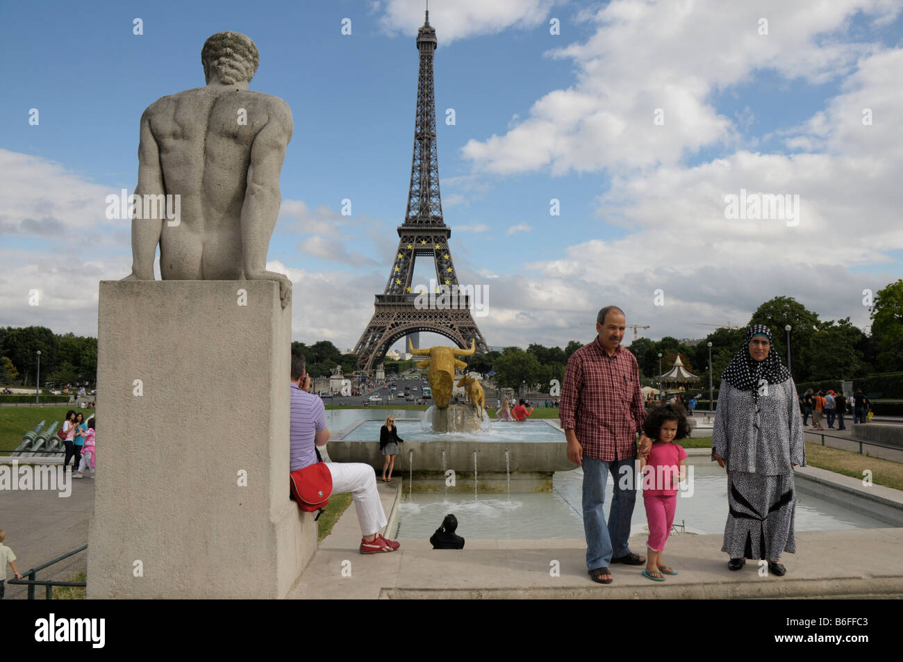 Immigrant family posing in front of the Eiffel Tower, Paris, France, Europe - Stock Image