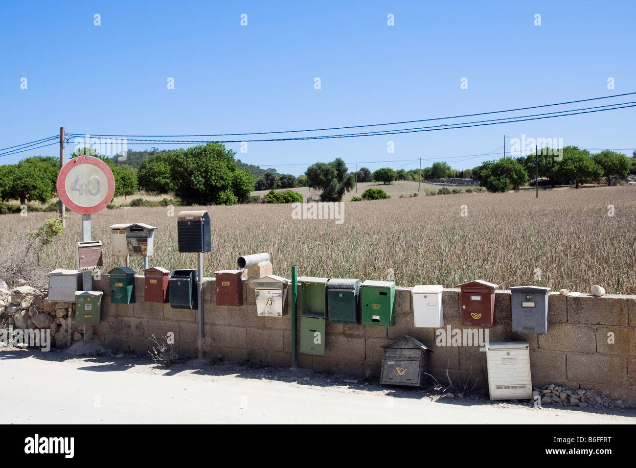 Letterboxes on a wall with a roadsign near Son Macia, Majorca, Balearic Islands, Spain, Europe Stock Photo