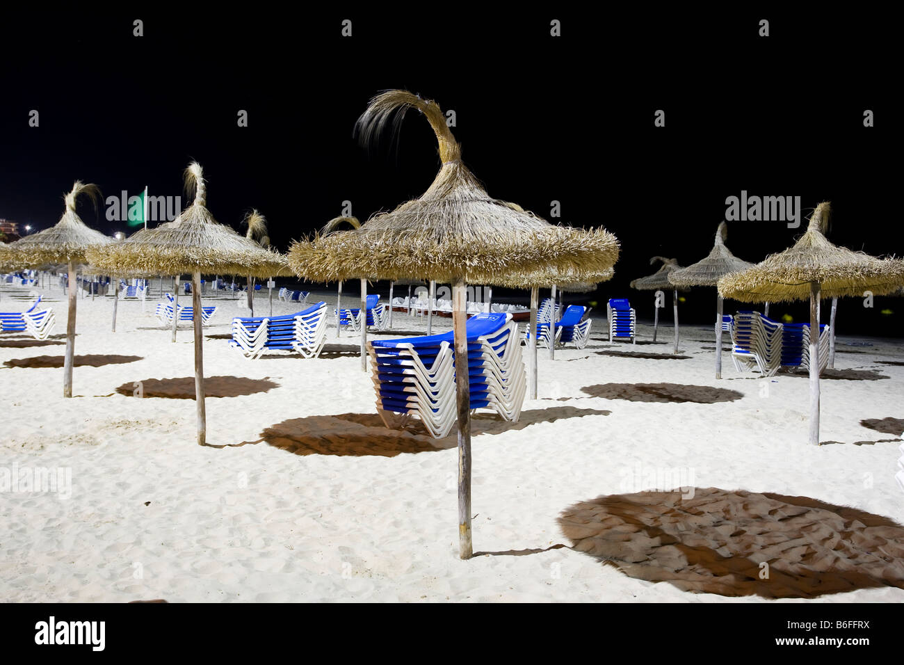 Sunshades and stacked deckchairs on the beach of Sa Coma at night, Majorca, Balearic Islands, Spain, Europe - Stock Image