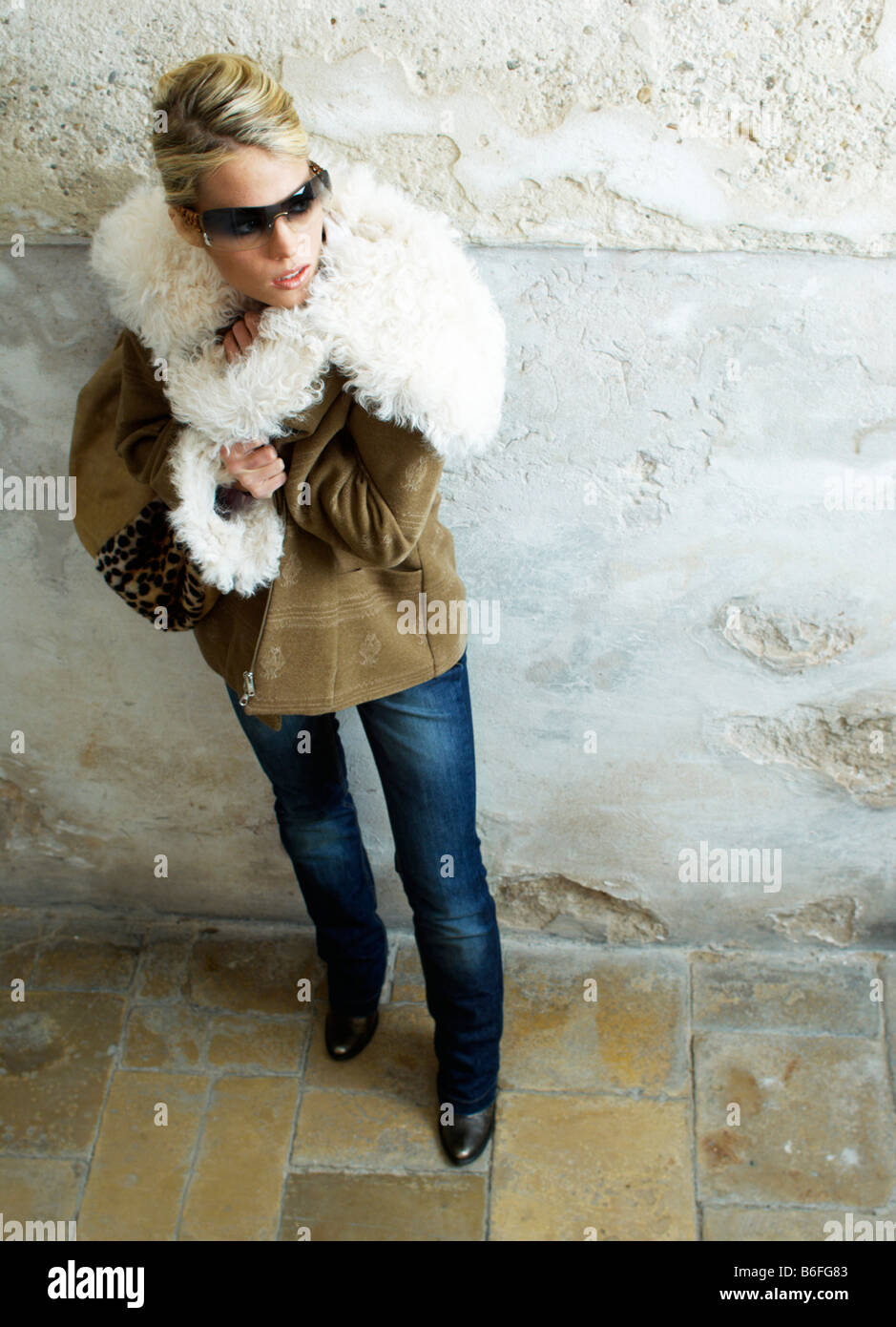 Young woman wearing a winter jacket standing in a stairwell - Stock Image