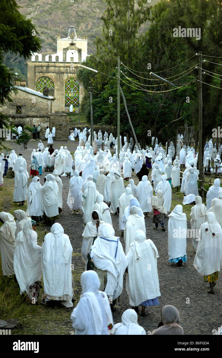 Procession of believers covered in white going to the old cathedral, Aksum, Ethiopia, Africa - Stock Image