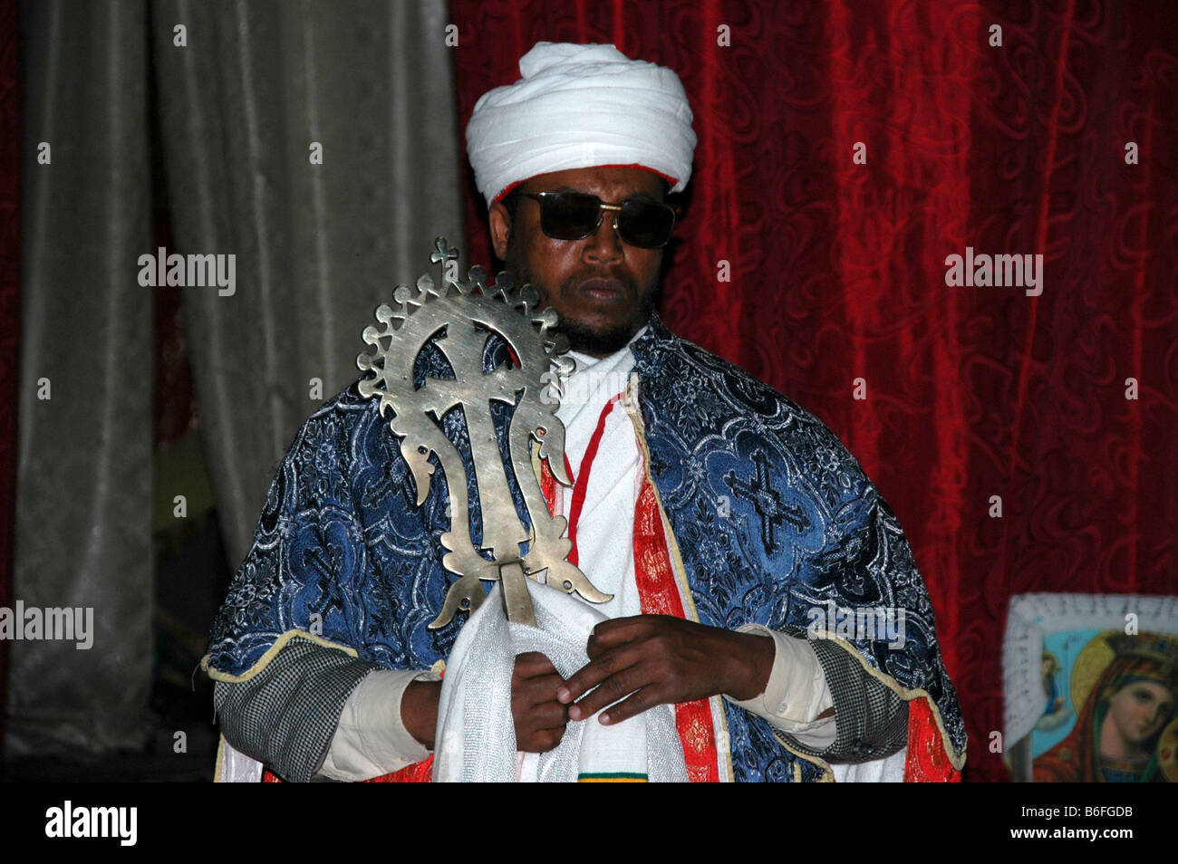 Priest wearing a white turban and cape carrying the Lalibela cross of gold, Beta Medhane Alem rock church, Lalibela, - Stock Image