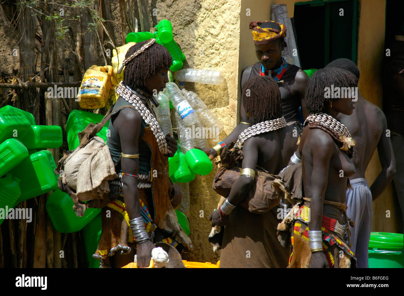 Black skinned Hamar people with white kauri mussel necklaces in front of green plastic canisters, market of Dimeka, - Stock Image