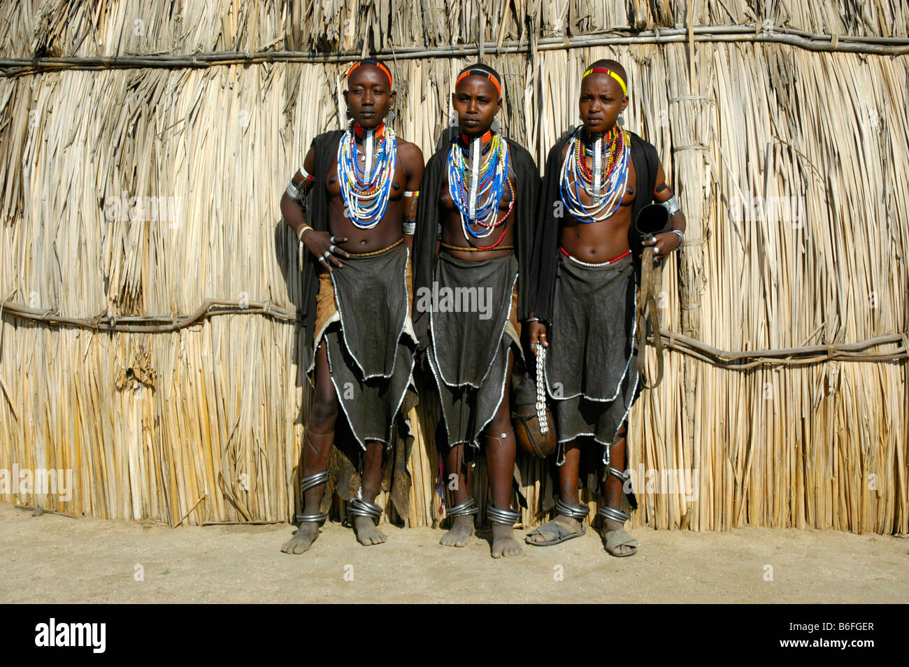 Three young women wearing leather skirts and lots of necklaces in front of straw hut, Erbore people, Weyto, Ethiopia, - Stock Image