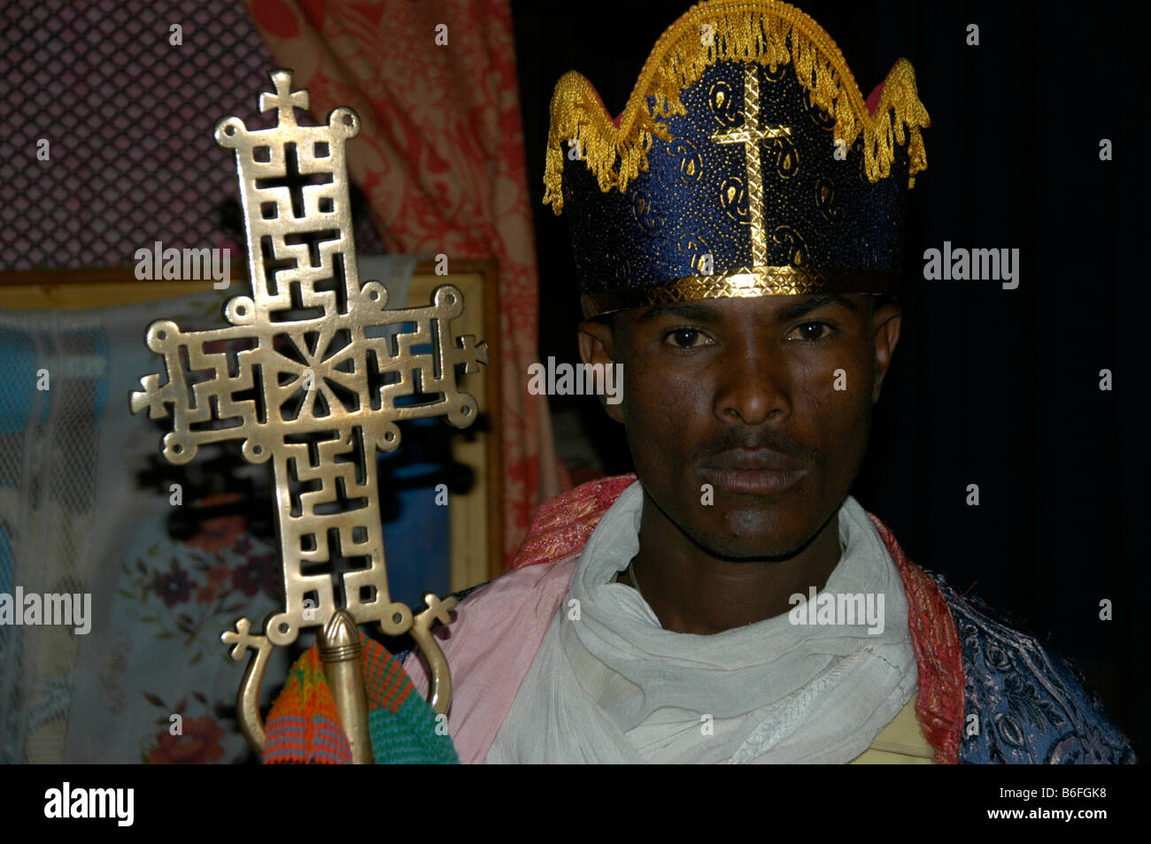 Priest wearing a headdress and holding an artfully decorated cross, Rock Church in Lalibela, Ethiopia, Africa Stock Photo
