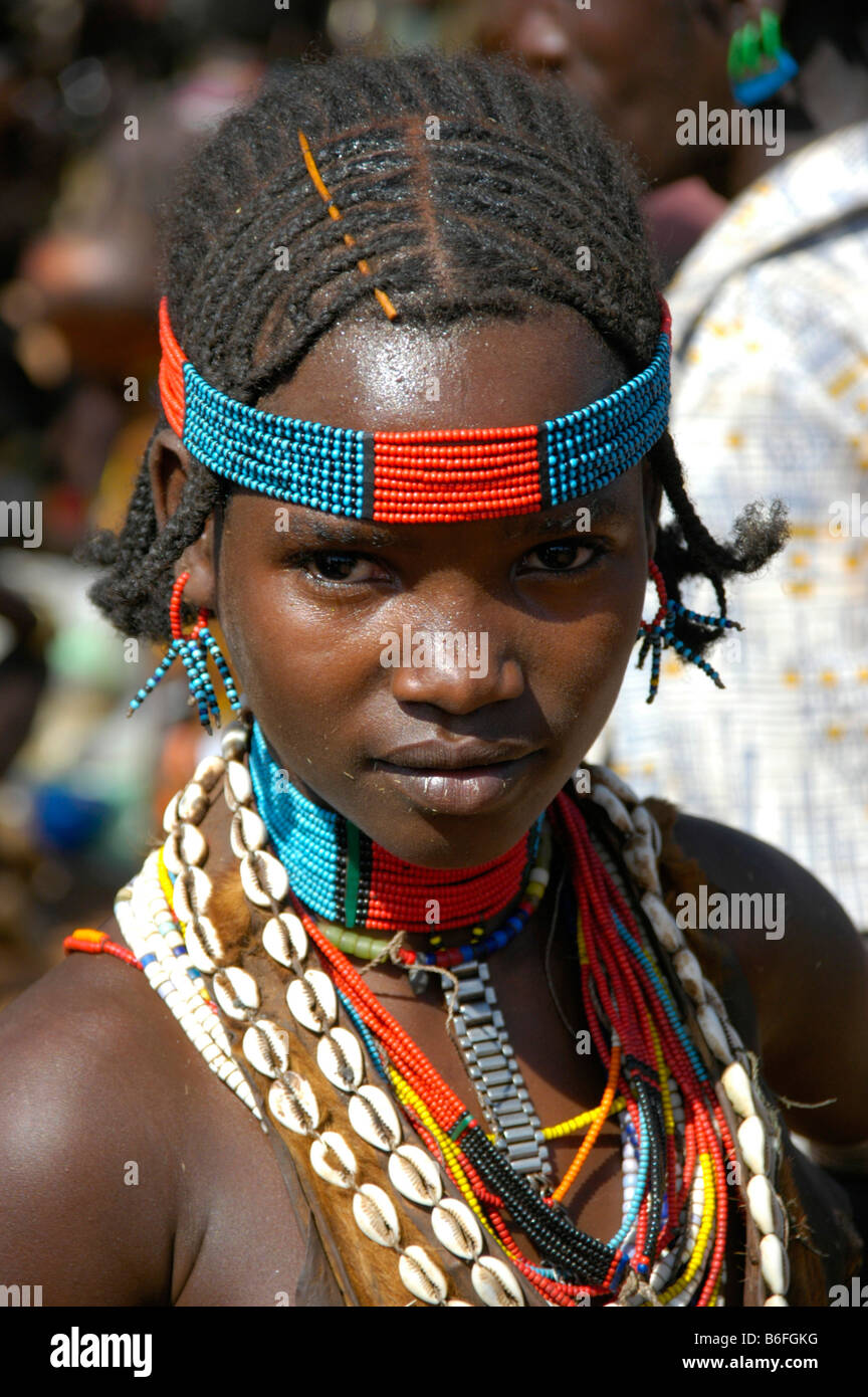 Girl wearing colorful bead head band and a necklace of kauri shells, portrait, at the markets in Dimeka, Ethiopia, - Stock Image
