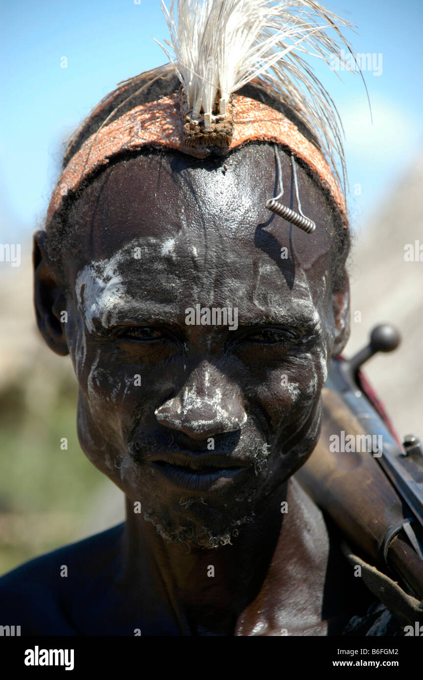Karo tribesman wearing feathers in a headband and white paint on his face and shouldering a rifle, portrait, Kolcho, - Stock Image