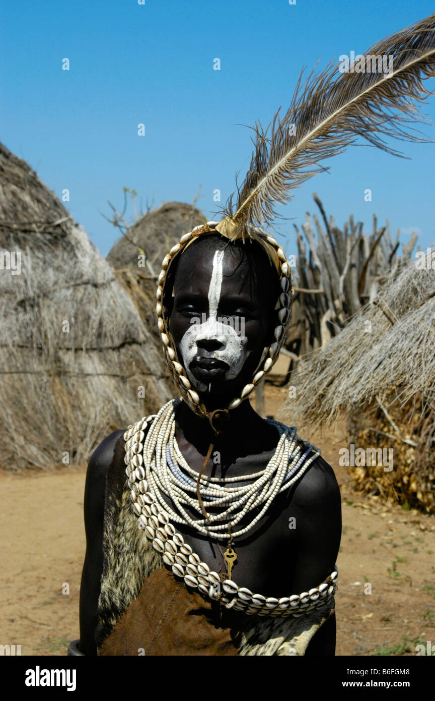 Young Karo tribesman wearing feathers in a headband and necklaces of Kauri Shells standing between straw huts, portrait, - Stock Image
