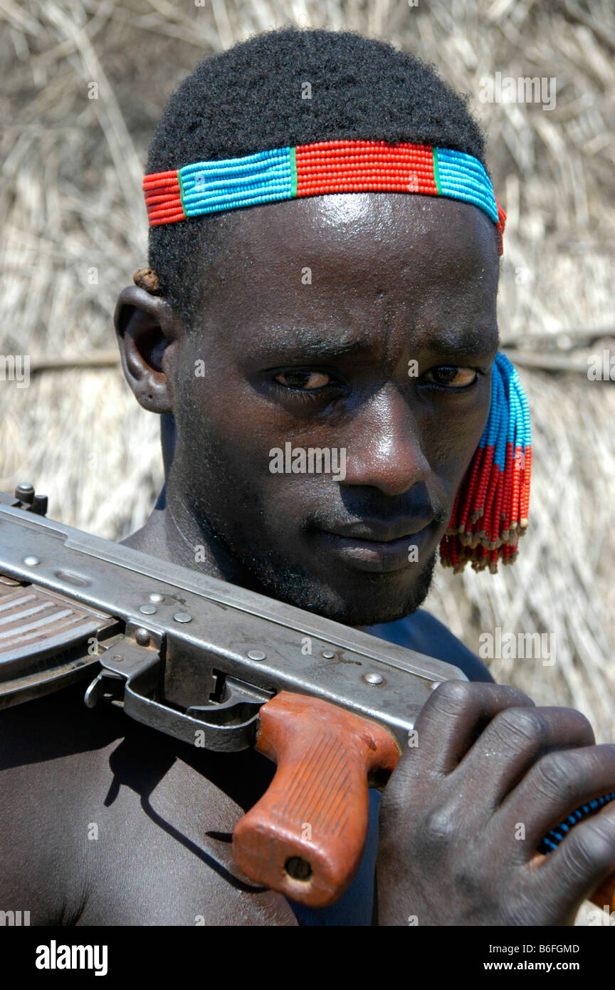Karo tribesman wearing a colorful headband shouldering a rifle, portrait, Kolcho, South Omo Valley, Ethiopia, Africa - Stock Image