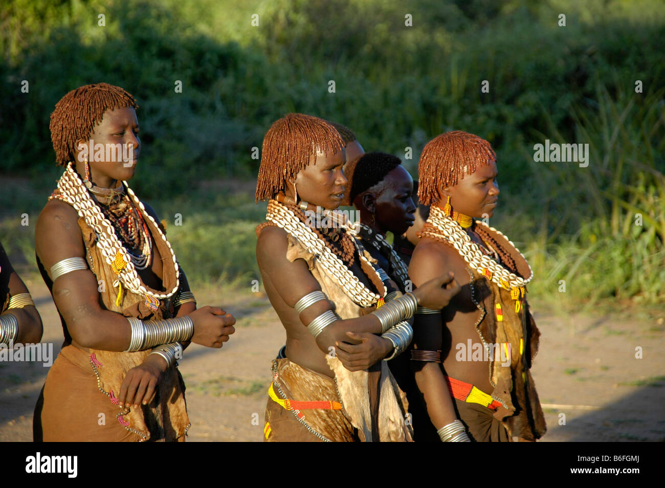 Young Hamar women wearing lots of armbands and necklaces standing in the dance area, near Turmi, Ethiopia, Africa - Stock Image