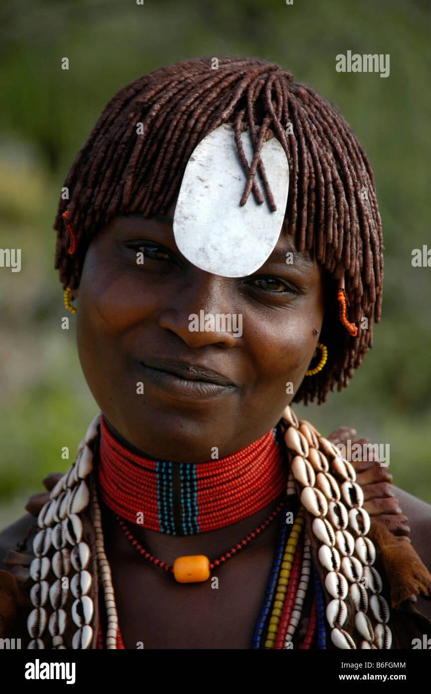 Smiling young black woman wearing a necklace of kauri shells, a flat metal plate on her forehead and clay in her - Stock Image