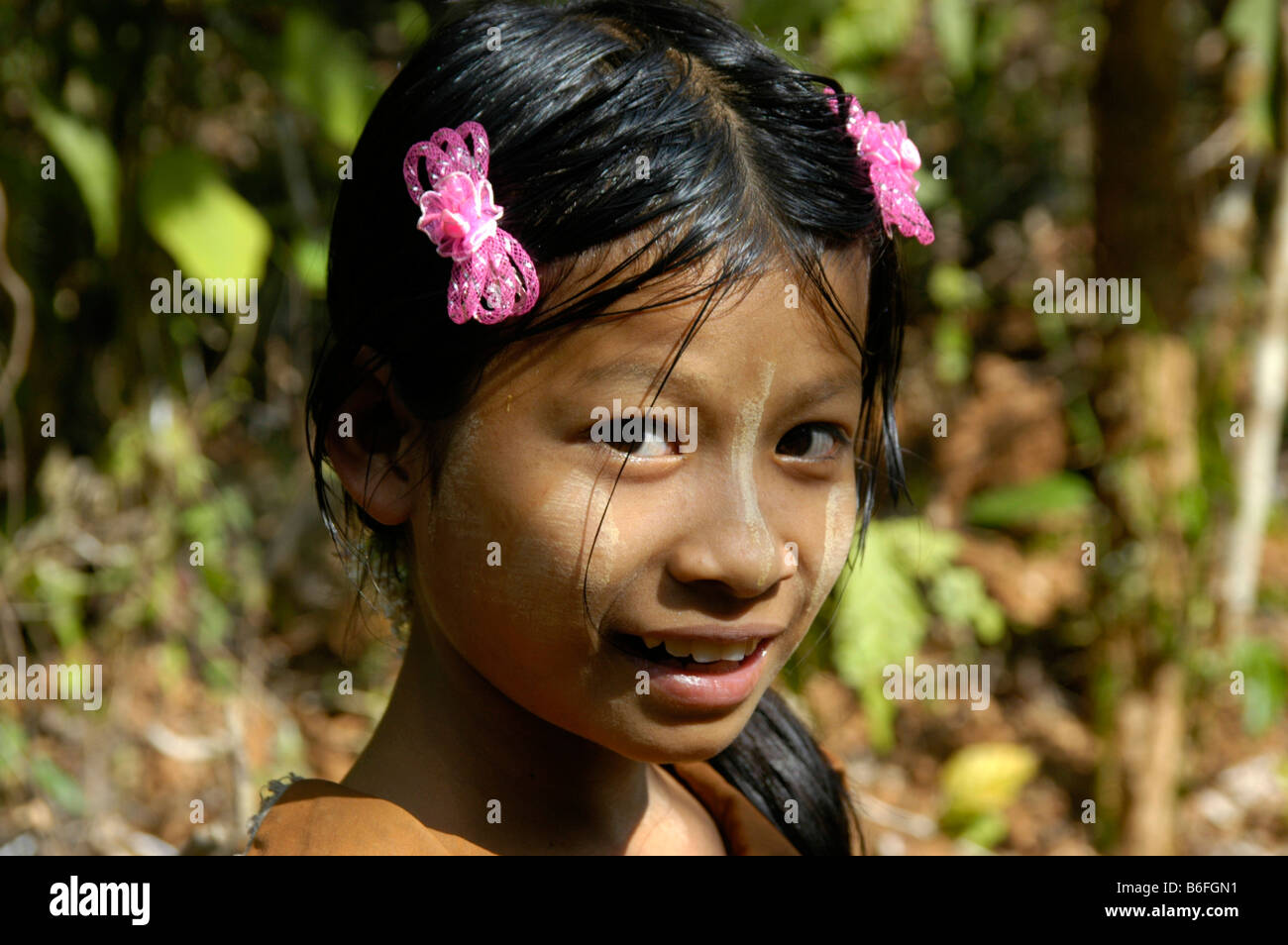 Smiling girl wearing bright pink hair-clips, portrait, Burma, Southeast Asia - Stock Image