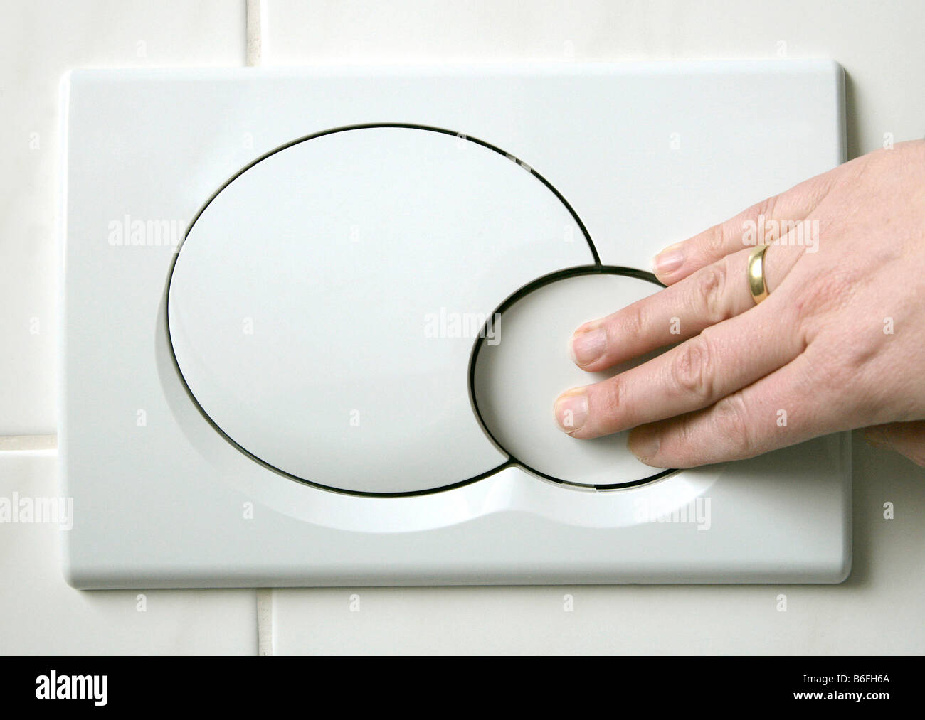 Hand pushing the low-flush button on a two button toilet flushing system, designed to reduce water usage, Regensburg, - Stock Image