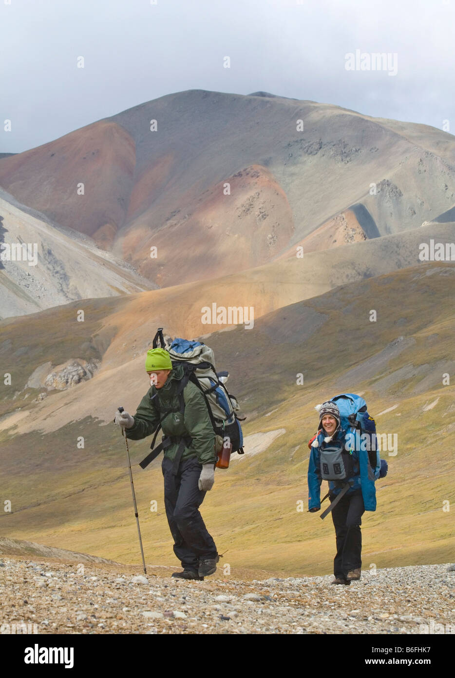 Two hikers, backpackers, women, ascending Hoge Pass, alpine tundra, Donjek Route, St. Elias Mountains, Kluane National - Stock Image