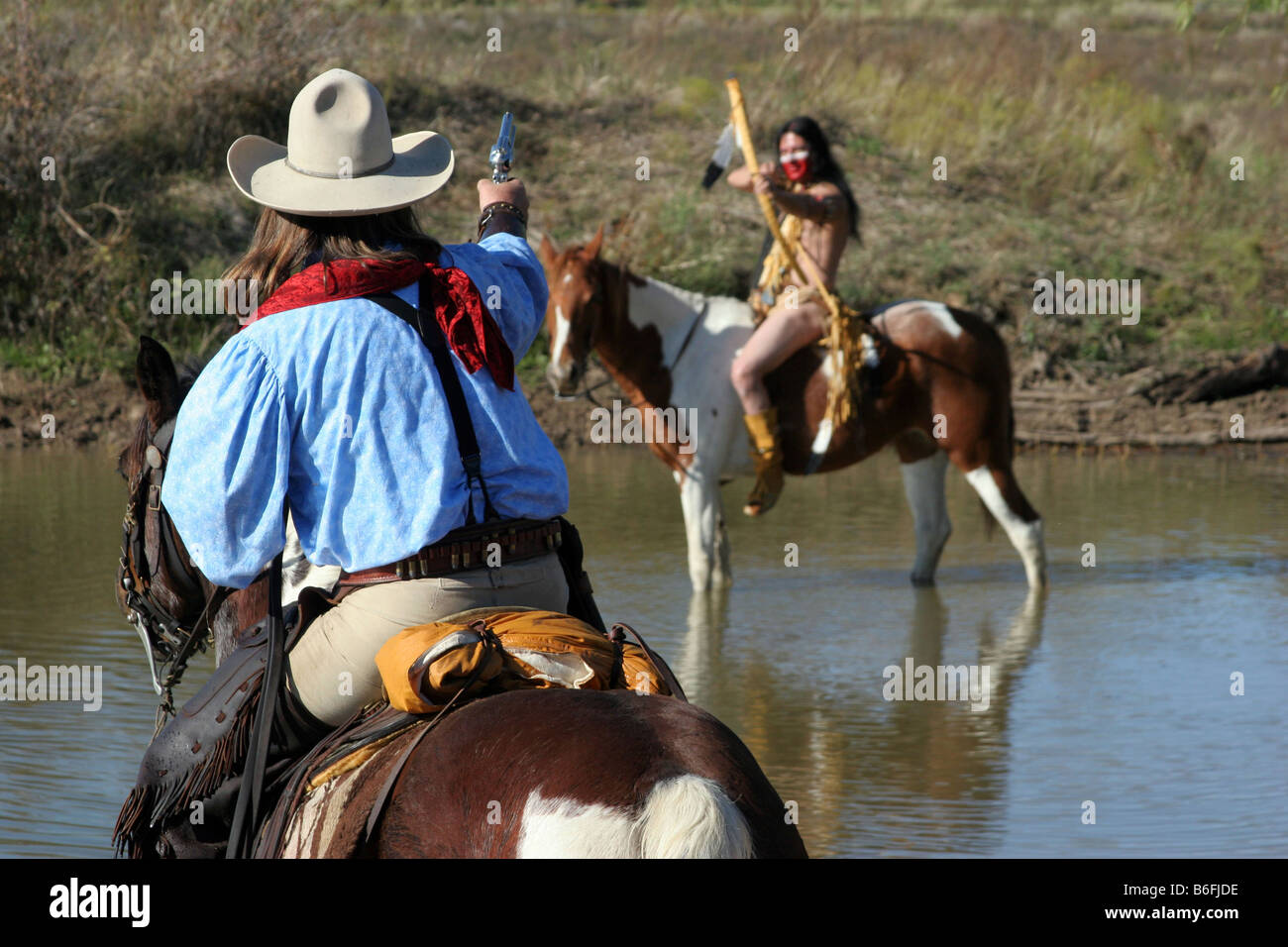 A cowboy and Native American face off across a body of water - Stock Image