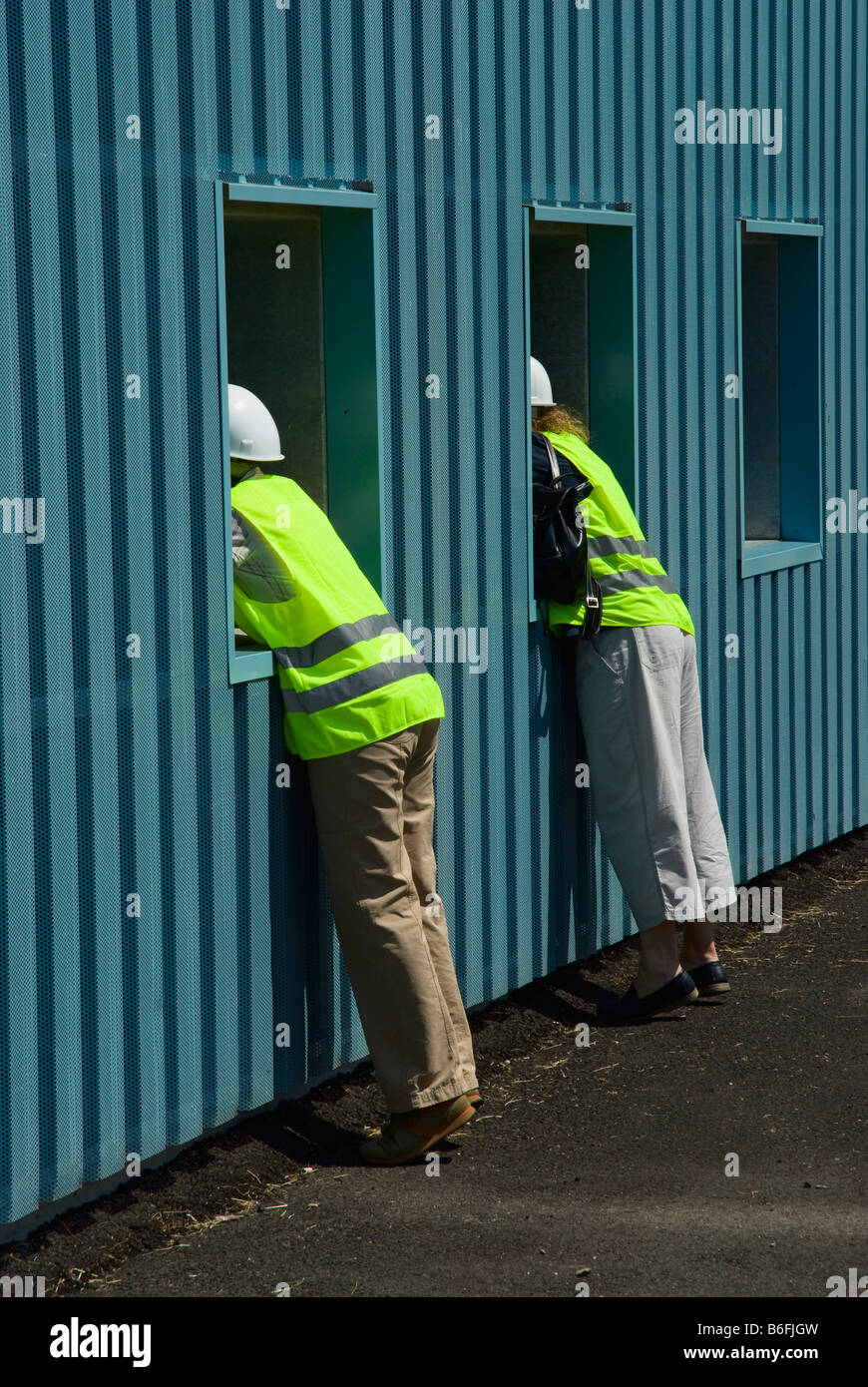 Visitors wearing hardhats and safety vests looking into the sanitation hall at the Sondermuelldeponie or hazardous - Stock Image