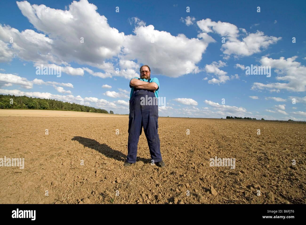 Farmer standing in a field - Stock Image
