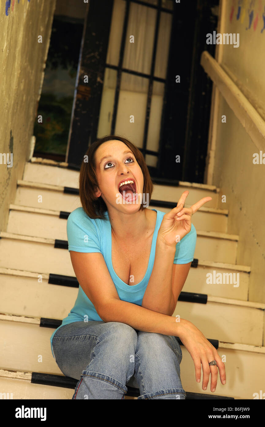 Teen girl on stairs flashing peace sign.