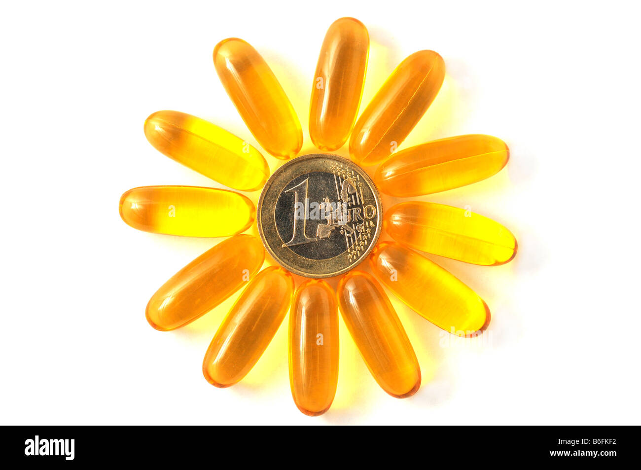 Medicine pills, capsules forming a flower in a ring around a coin - Stock Image