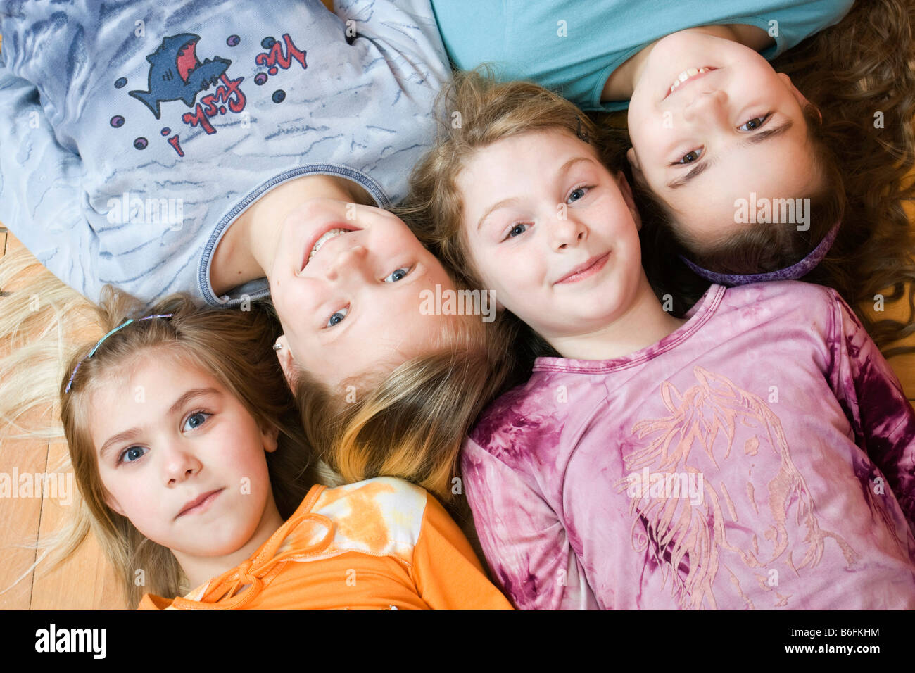 Group of four little girls lying on the floor, from the left 6, 11, 9 and 10 years old, bird's-eye view Stock Photo
