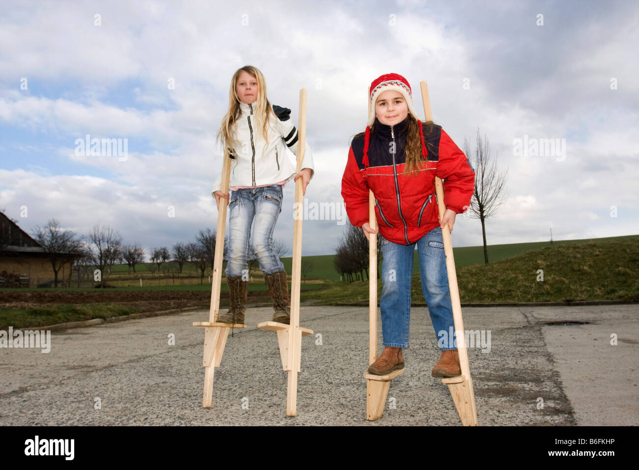Little girls, 11 and 10 years old, on stilts, outside Stock Photo