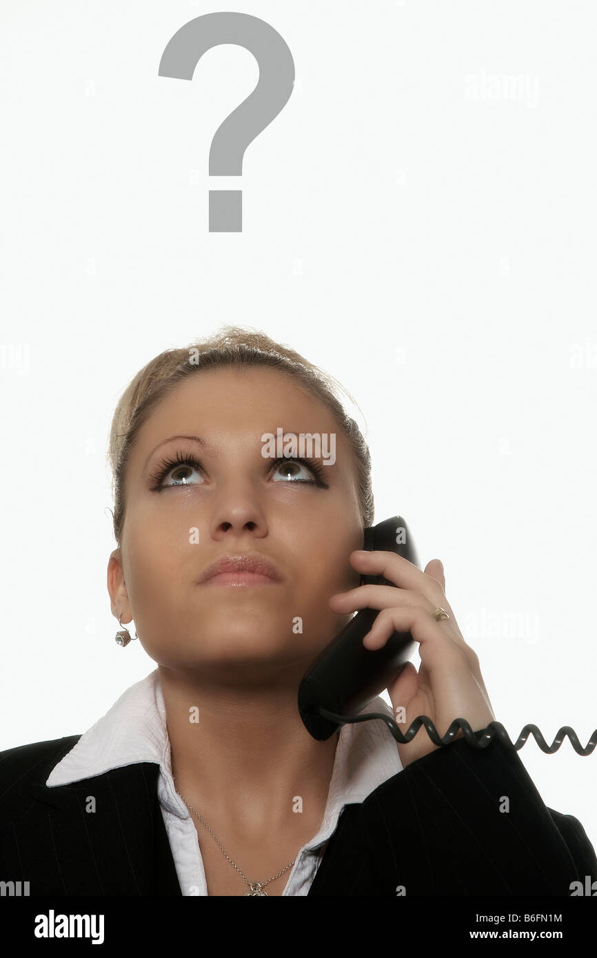 Businesswoman with a telephone in her hand, a question-mark above her head - Stock Image