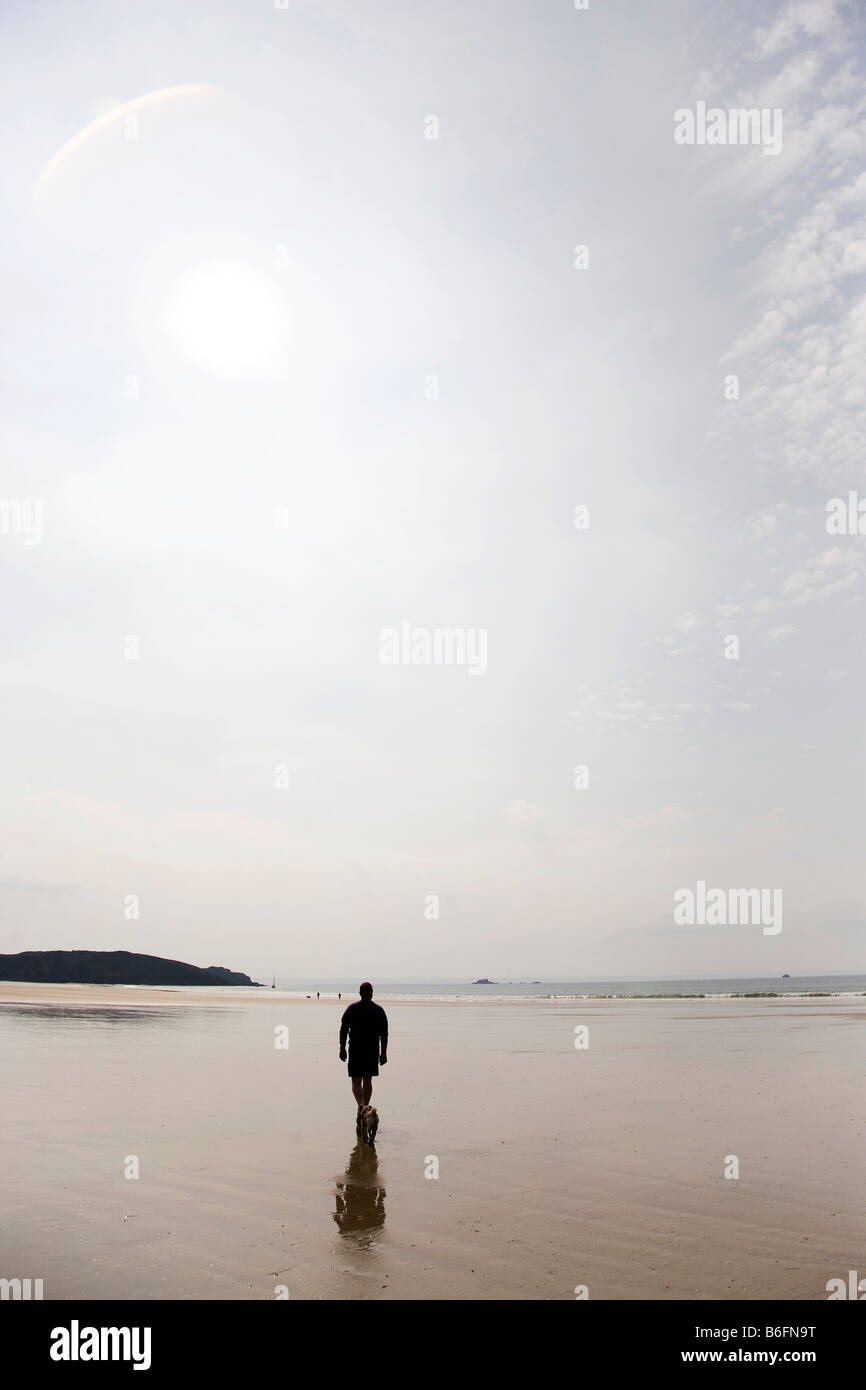 Backlit man on the beach, dull day - Stock Image