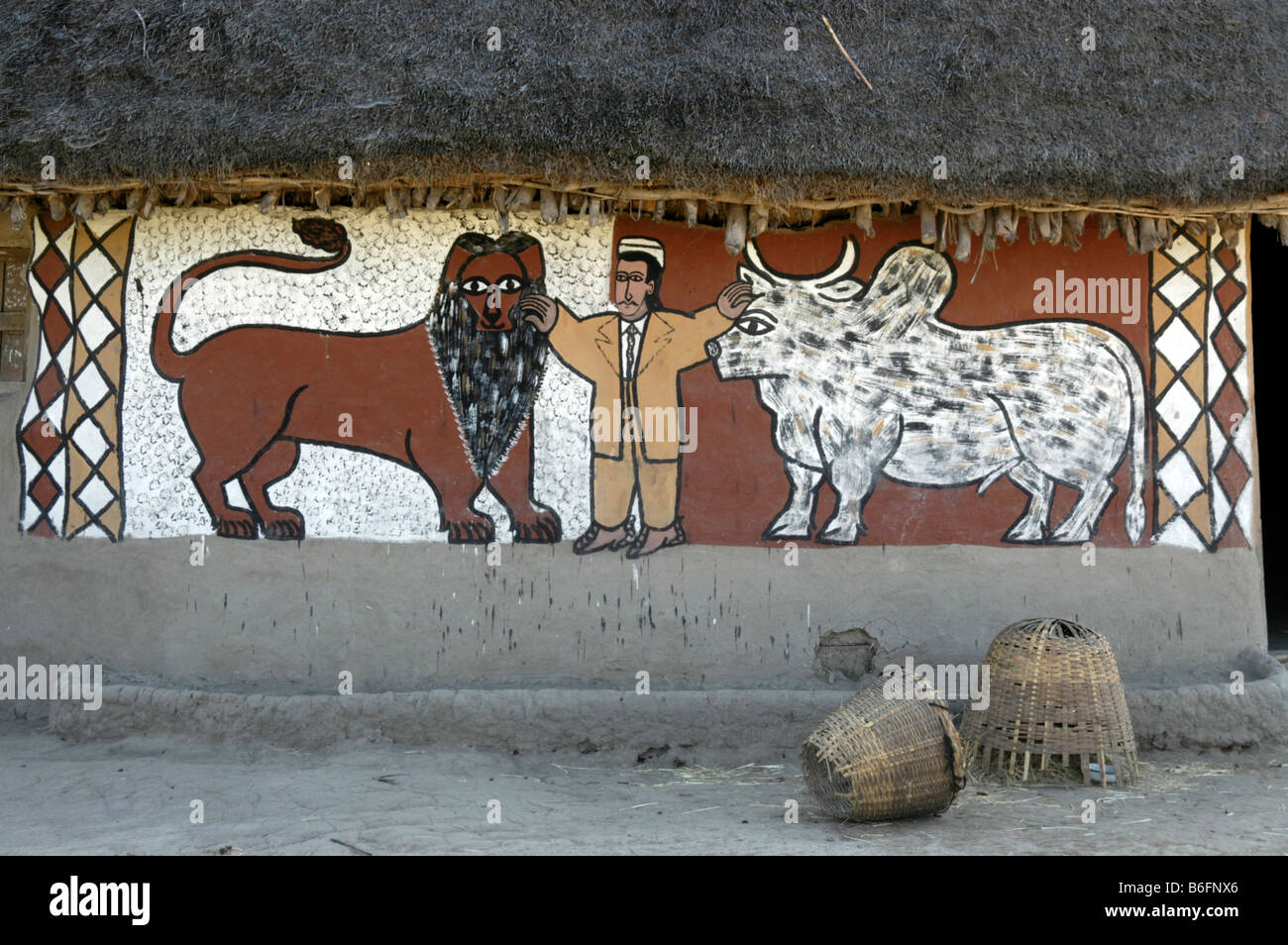 Mural of a man standing between a lion and an oxen on the exterior wall of an earth house, Ethiopia, Africa - Stock Image